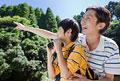タイトル:屋外で遠くを見つめる父親と息子