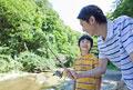 タイトル:渓流で釣りをする父親と息子