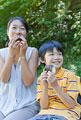 タイトル:屋外でおにぎりを食べる母親と息子