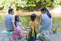 タイトル:川辺で弁当を食べる家族4人