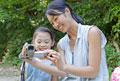 タイトル:屋外でビデオカメラを見る母親と娘