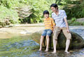 タイトル:渓流の岩に腰掛ける父親と息子