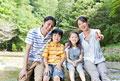 タイトル:渓流の岩に腰掛ける親子4人
