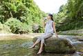 タイトル:渓流の岩に腰掛けて水を飲む女性