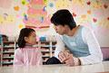 タイトル:女の子とにらめっこをする幼稚園教諭