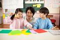 タイトル:折り紙をする子供2人と幼稚園教諭