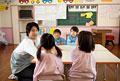 タイトル:教室で話をする幼稚園児と幼稚園教諭