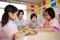 タイトル:折り紙をする子供3人と幼稚園教諭