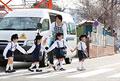 タイトル:バスの前を並んで歩く幼稚園児と幼稚園教諭
