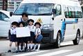 タイトル:バスの前でホワイトボードを持つ幼稚園児と幼稚園教諭