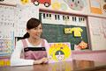 タイトル:紙芝居を見せる幼稚園教諭