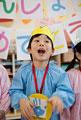タイトル:メダルと王冠を着けて歌う男の子