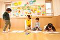 タイトル:教室でお絵描きをする子供3人と保育士