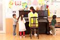 タイトル:ピアノで遊ぶ子供3人と保育士