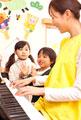タイトル:ピアノで遊ぶ子供2人と保育士