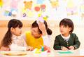 タイトル:折り紙で遊ぶ子供2人と保育士