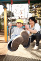 タイトル:ブランコで遊ぶ男の子と保育士