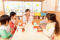 タイトル:食事の挨拶をする子供4人と保育士