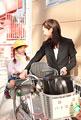 タイトル:自転車に子供を乗せて歩く母親