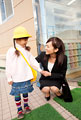 タイトル:保育所の前でしゃがむ母親と子供