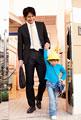 タイトル:手を繋いで歩く父親と子供