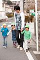 タイトル:外を散歩する子供3人と保育士