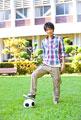 タイトル:サッカーボールを足元に置く男子大学生