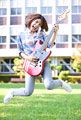 タイトル:ギターを持ってジャンプする女子大学生