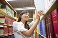 タイトル:図書館で本を探す女子大学生