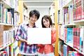 タイトル:図書館でメッセージボードを持つ大学生