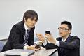 タイトル:スマートフォンを見せ合うビジネスマン2人