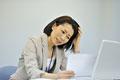 タイトル:書類を見て困った表情をする女性