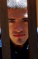 Man peering through bars