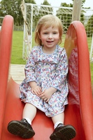 Beautiful toddler blond girl playing on the park playground
