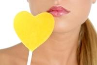 Heart shape candy on beautiful woman macro mouth