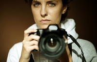 young woman with black slr camera, natural light, selective focus on eye