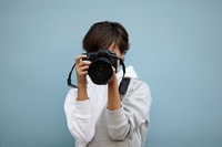 young woman with professional camera, selective focus on nearest part of lens