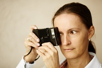 Woman with old film camera, focus point on eye, natural light