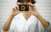 young woman with small plastic photocamera, selective focus on foreground