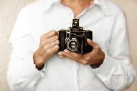 Woman hands with old film camera, selective focus point on lens, natural light