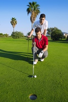 young man playing golf looking and aiming for the hole