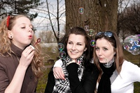 Teenage girls having fun with soap bubbles in the park