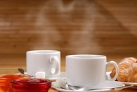 Coffee cup and croissants with jelly on the wooden table, steam has heart shape