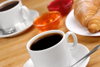 Coffee cup and croissants with jelly on the wooden table