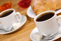 Coffee cups and croissants with jelly on the wooden table