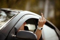 young driver shows middle finger, natural light, selective focus