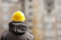 real builder with yellow hardhat, natural light, selective focus on part of hood and helmet