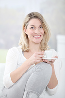 Blond woman in sofa holding coffee cup