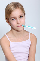 Portrait of little girl with thermometer into mouth