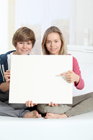 Smiling teenagers sitting in sofa with whiteboard